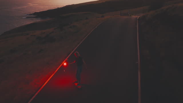 Young woman skateboarding at dusk with glowing red flare video