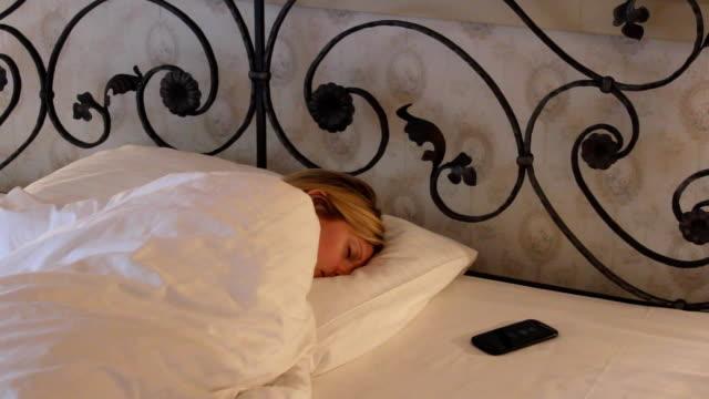 stockvideo's en b-roll-footage met jonge vrouw slapen in bed, mobiele ring en ze wakker worden - s