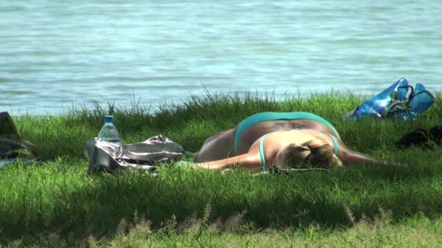 Joven mujer durmiendo sobre la hierba cerca thè al mar - vídeo