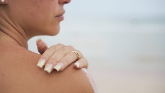 Young Woman Smearing Shoulders With Sun Cream At Beach video
