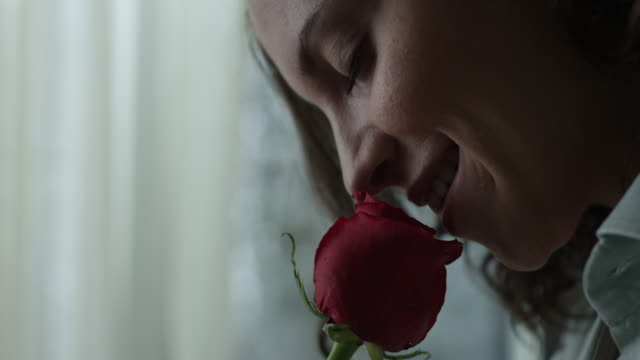 Young woman smelling red rose video
