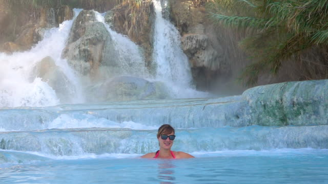 SLOW MOTION: Young woman smiles as she relaxes in the hot thermal spring water. SLOW MOTION: Young Caucasian woman smiles as she relaxes in hot thermal spring water in cool outdoor spa. Cheerful girl with sunglasses enjoying a relaxing bath in refreshing natural pools in Italy. natural condition stock videos & royalty-free footage