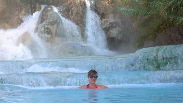 スローモーション: 若い女性の笑顔彼女は熱い温泉水でリラックス、. ビデオ