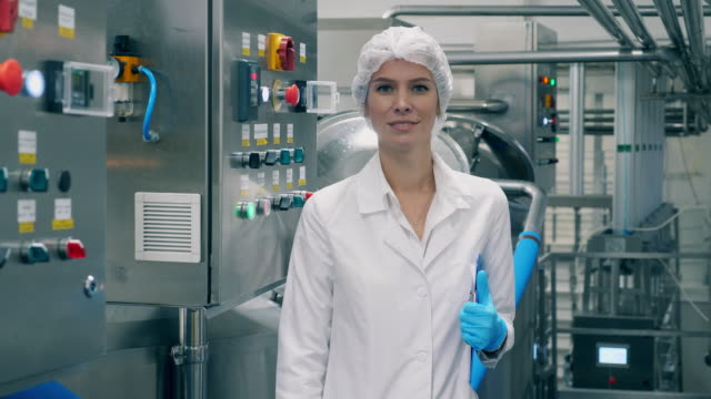 Young woman smiles at camera, standing in a facility.