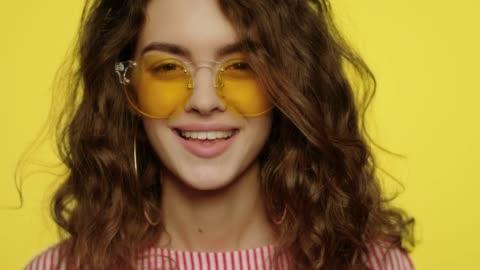 junge frau lächelt auf gelbem hintergrund porträt des glücklichen mädchens lächelnd - gelb stock-videos und b-roll-filmmaterial