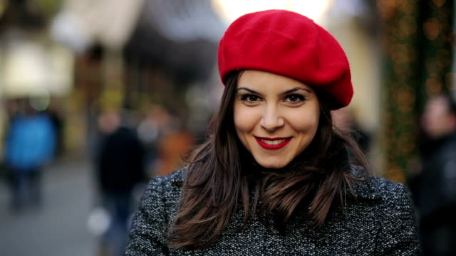 young woman smiling portrait of a beautiful young smiling  woman with red hat in the street brown hair stock videos & royalty-free footage