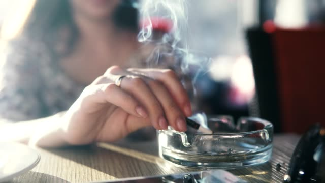 a young woman smokes in a cafe. - sigaretta video stock e b–roll