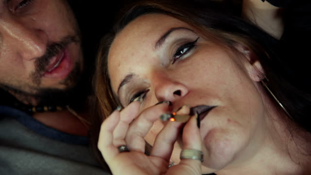 Young Woman Smoking Marijuana Cigarette With Boyfriend At Home Substance abuse, drugs and people, boyfriend and girlfriend smoking hashish joint at home. Young man and woman using marijuana hippie stock videos & royalty-free footage