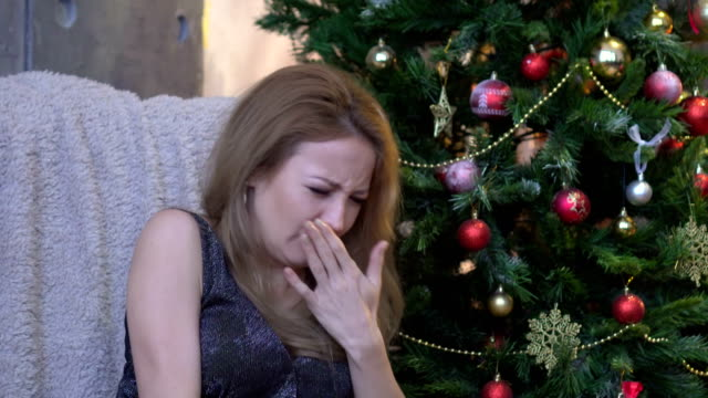 Young woman sneezing on christmas tree background. video