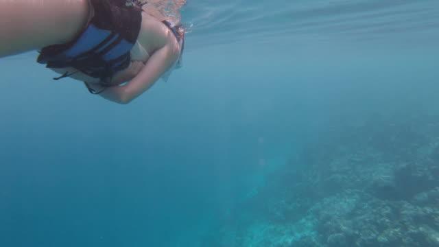 Young woman snorkeling in a paradisiac sea at Maldives