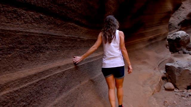 stockvideo's en b-roll-footage met jonge vrouw die zacht vlotte rotsachtige muur op dorre canion raakt - geologie