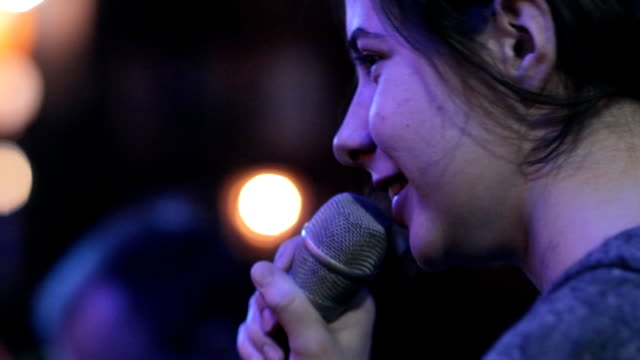 A young woman soloist sings a song at a concert. video