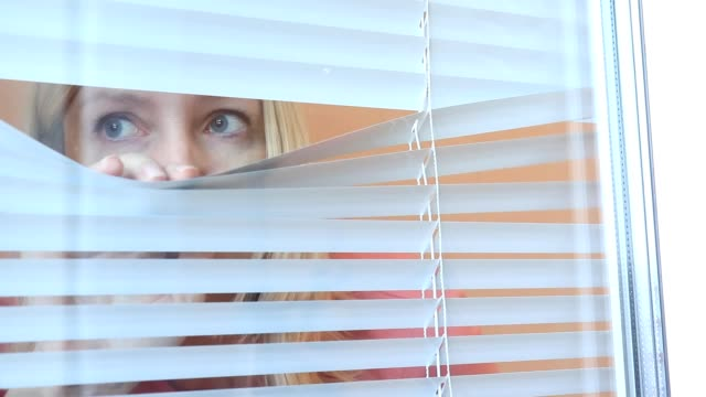 Young woman spying, peeking through the blinds in her home Young woman spying, peeking through the blinds in her home hiding stock videos & royalty-free footage
