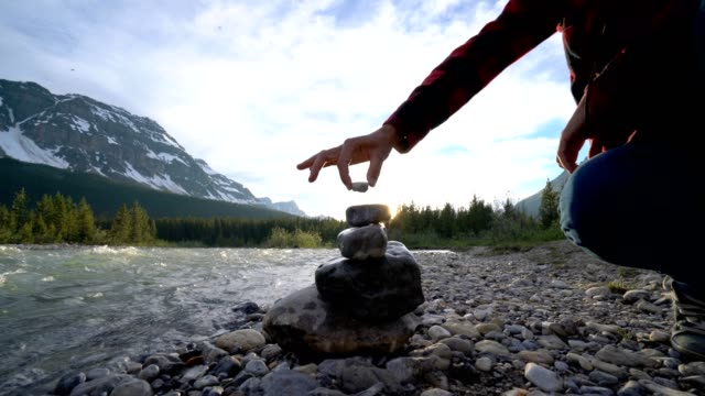 young woman stacking rocks by the river, canada - 4k - alternative medicine stock videos and b-roll footage