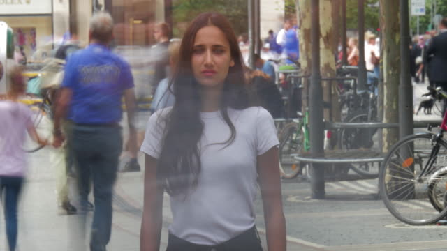 Young Woman Standing Amidst City Crowd Time Lapse Young woman standing in crowd as unrecognizable blurred people move about in fast motion. Time lapse. Medium shot. standing stock videos & royalty-free footage