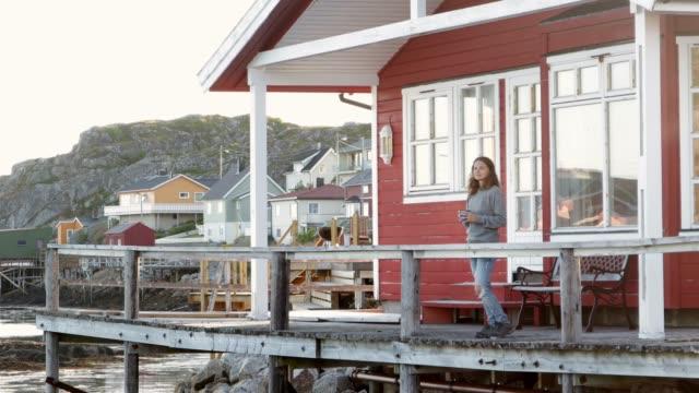 eine junge frau steht bei sonnenuntergang auf der terrasse der fischerhütten und genießt die aussicht. - blockhütte stock-videos und b-roll-filmmaterial