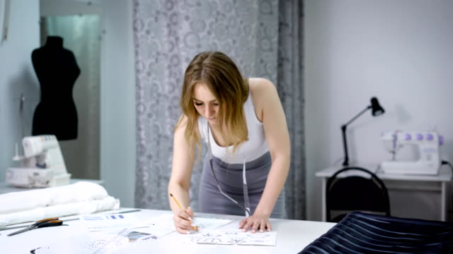 Young woman standing bending over the table in tailoring studio and sketching future dresses. Designer creating new fashion collection. Female dressmaker is working in atelier drawing pattern video