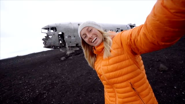 Young woman standing by airplane wreck on black sand beach taking a selfie portrait Famous place to visit in Iceland and pose with the wreck-Slow motion video