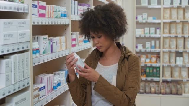 ds junge frau steht am regal in der apotheke und liest das etikett auf der rückseite der medikamentenflasche - etikett stock-videos und b-roll-filmmaterial