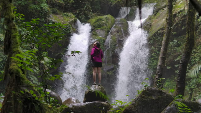 Young Woman Standing By the Waterfall and Embracing in Slow motion