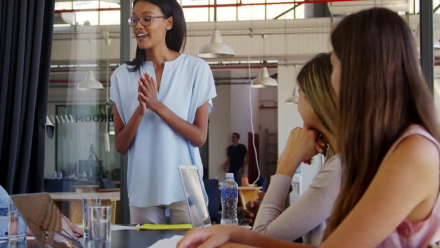 Young woman standing claps with seated colleagues at meeting - Vidéo