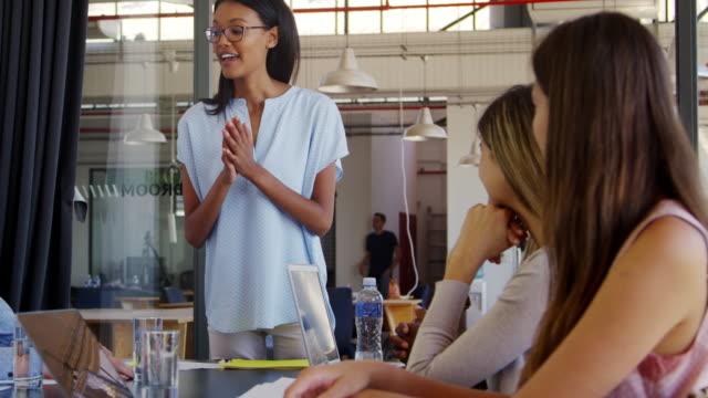 Jeune femme debout claps avec des collègues assis à la réunion - Vidéo