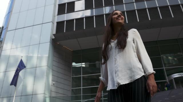 young woman standing in awe beneath skyscrapers - hindus filmów i materiałów b-roll