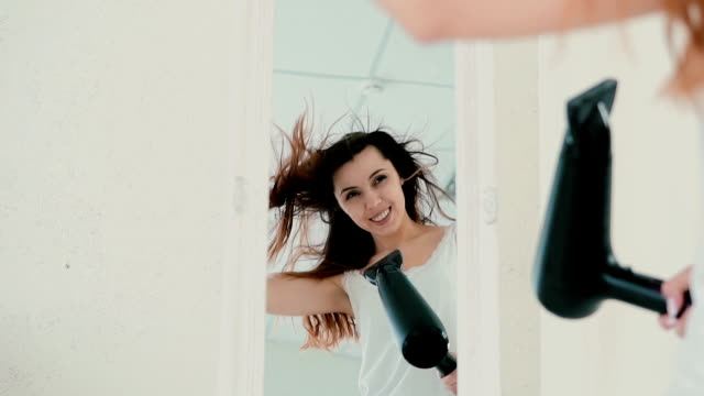 Young woman standing in front of mirror in pajamas. Girl using hair dryer and sing, wind blowing the hair. Slow motion video