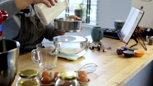 Young woman standing in the kitchen and sifting flour in the bowl. Blonde female weighing the ingredients for cooking video
