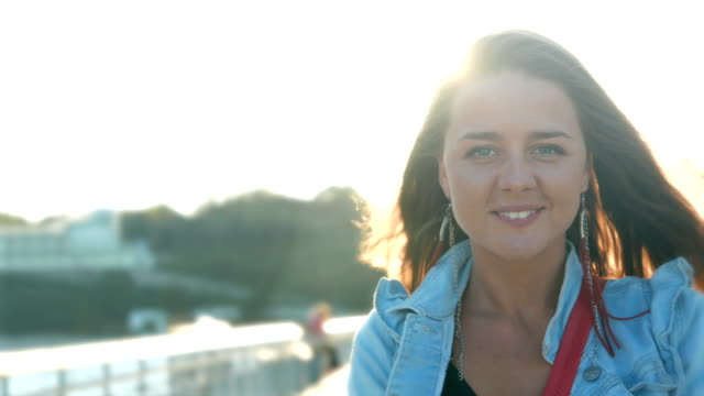 Young woman standing near the sea and looking at camera video