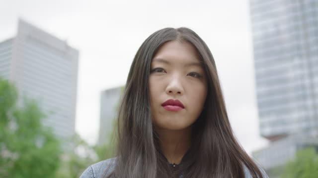 Young woman standing next to skyscraper video
