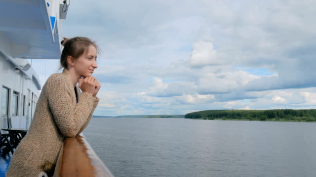 Young woman standing on deck of cruise ship and looking at river and landscape video