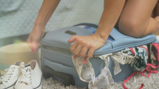 Young woman standing on her knees on overfilled suitcase, trying to close it. Young woman standing on her knees on overfilled suitcase, trying to close it. stuffed stock videos & royalty-free footage