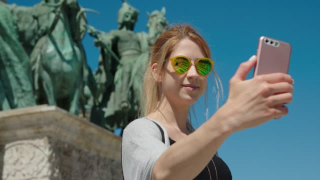 Young woman standing on Heroes' Square and taking a selfie Tourist girl taking photos of monuments with her smart phone in European city. hungary stock videos & royalty-free footage