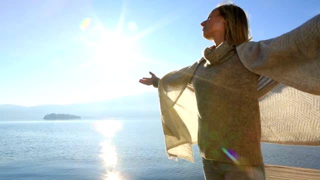 vídeos de stock e filmes b-roll de young woman standing on pier, harms raised - lago maggiore