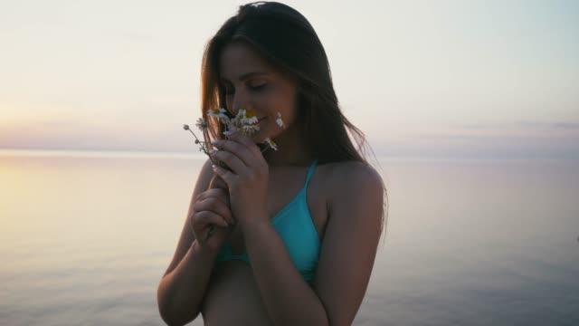 vídeos y material grabado en eventos de stock de mujer joven de pie en la orilla del mar y oler flores. usar bikini y pantalones cortos - manzanilla