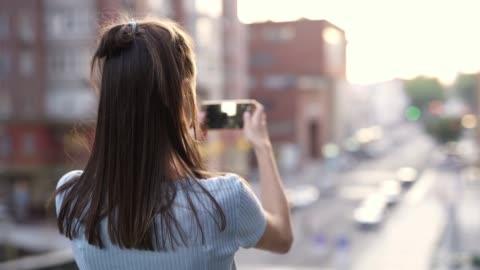 giovane donna in piedi sullo sfondo della strada della città al tramonto e scattare foto o video utilizzando lo smartphone - filmare video stock e b–roll