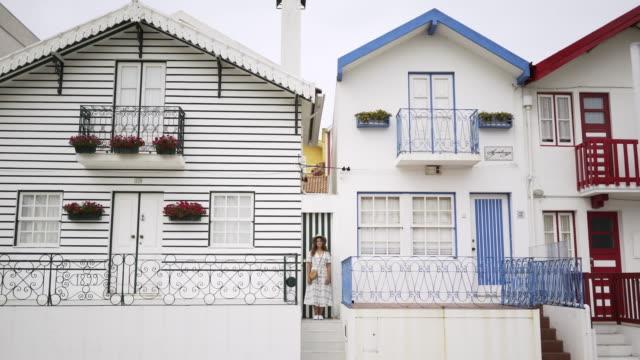 vídeos de stock e filmes b-roll de young woman standing on the doorstep of pretty house - aveiro