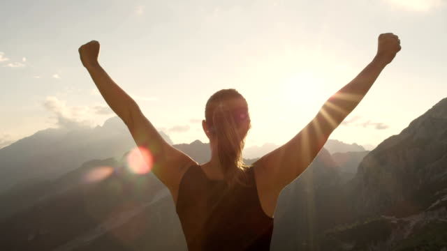 CLOSE UP: Young woman standing on the edge of the mountain with hands raised