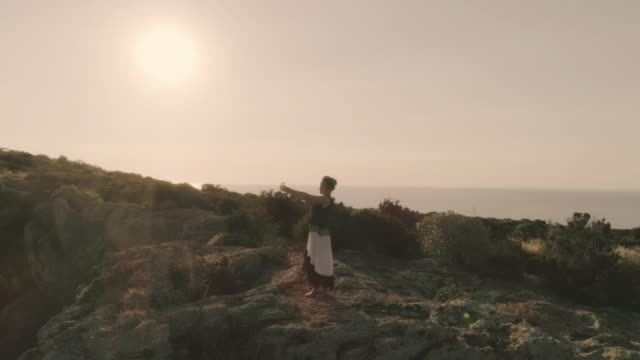 Young woman standing on top of a cliff on an island taking pictures of the ocean with her tablet video
