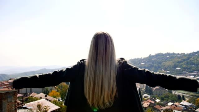 Junge Frau hob hob Hände Blick auf Dorf und Berge Gipfel Hintergrund erstaunliche Landschaft. Zufrieden Frischluft atmen Mädchen voll zurück sehen. – Video