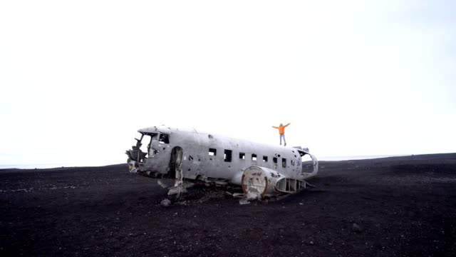 Young woman stands arms outstretched on airplane crashed on black sand beach looking around her contemplating surroundings Famous place to visit in Iceland and pose with the wreck- 4K video video