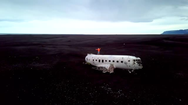 Young woman stands arms outstretched on airplane crashed on black sand beach looking around her contemplating surroundings Famous place to visit in Iceland and pose with the wreck 4K video video
