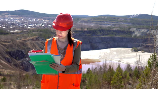 vídeos de stock e filmes b-roll de a young woman stands at an open quarry with a pad and documents on a sunny day. - geologia