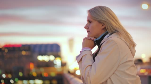 A young woman stands leaning on the railing of the bridge, admiring the beautiful sunset