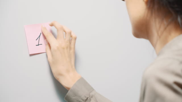 Young woman sticking pink reminder stickers with numbers 1 2 3 on a gray board. Copy space.
