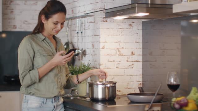 vídeos y material grabado en eventos de stock de la mujer joven agita la comida en la sartén mientras sostiene su smartphone y sonríe. - woman cooking