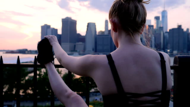 Young woman stretching against the New York City waterfront sunset video