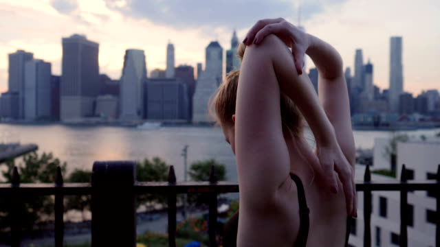 young woman stretching against the new york city waterfront sunset - reggiseno sportivo video stock e b–roll