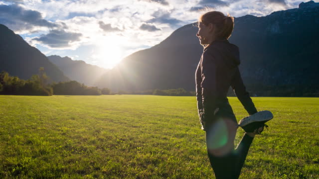 Young woman stretching in the mountainside video